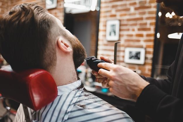 Barbeiro corta barba para um cara brutal