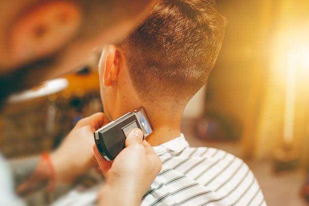 Barbeiro corta o cabelo na cabeça com navalha