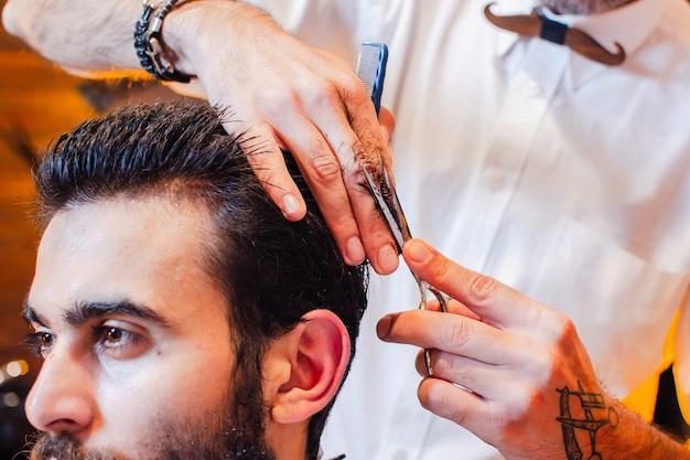 Barbeiro corta o cabelo na cabeça