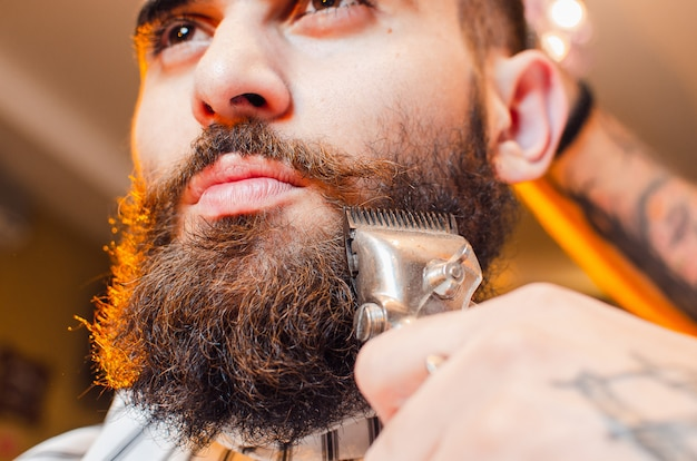 Barbeiro corta uma barba de tosquiadores de cabelo vintage