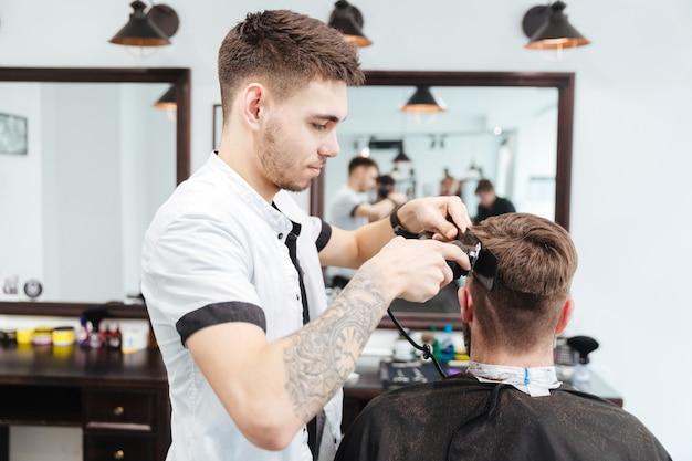 Barbeiro cortando cabelo com barbeador elétrico em barbearia