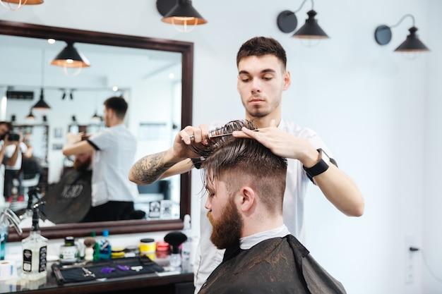 Barbeiro cortando cabelo com tesoura para seu cliente na barbearia
