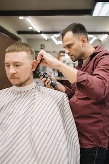 Barbeiro dando um corte de cabelo na barbearia