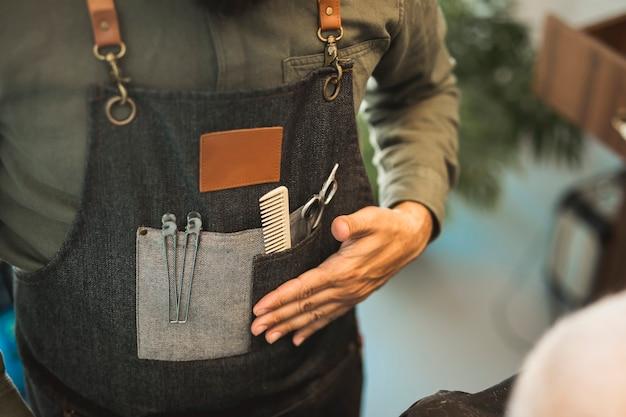 Barbeiro de avental com ferramentas para cortar o cabelo