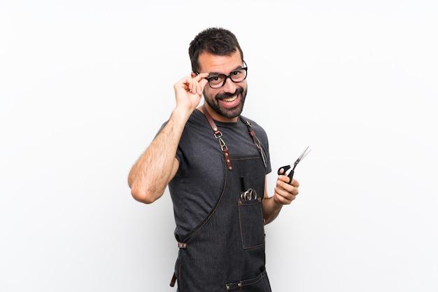 Barbeiro de avental com óculos e sorrindo