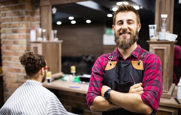 Barbeiro de avental com os braços cruzados e feliz na barbearia