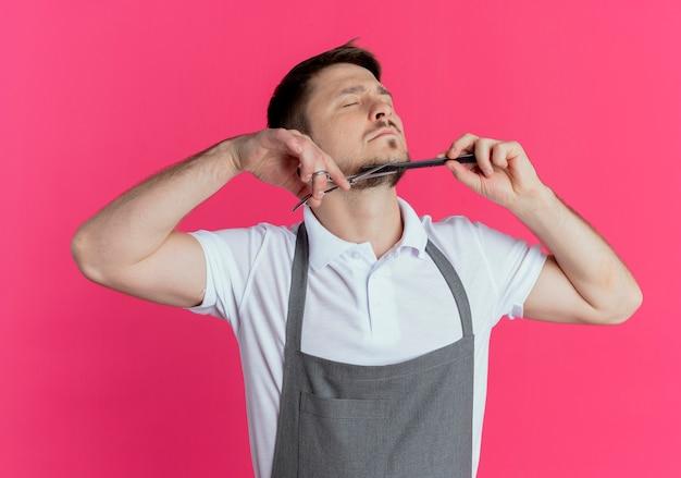 Barbeiro de avental cortando a barba com uma tesoura em pé sobre um fundo rosa
