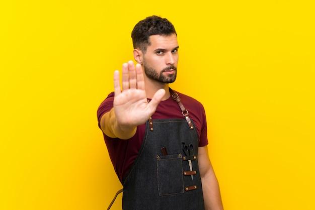 Barbeiro de avental, fazendo o gesto de parada com a mão