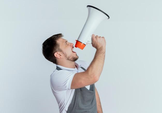Barbeiro de avental gritando ao megafone com expressão agressiva em pé sobre uma parede branca