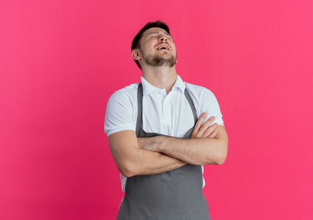 Barbeiro de avental incomodado e cansado com os braços cruzados em pé sobre a parede rosa