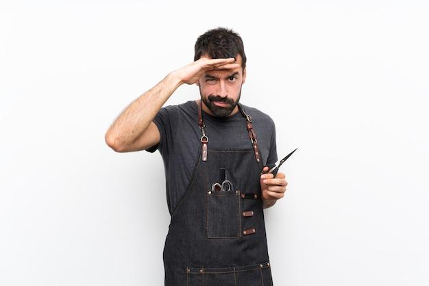 Barbeiro de avental olhando longe com a mão para procurar algo