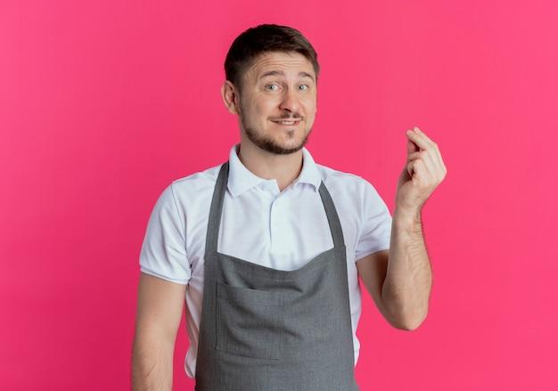 Barbeiro de avental olhando para a câmera esfregando os dedos e pedindo dinheiro em pé sobre fundo rosa