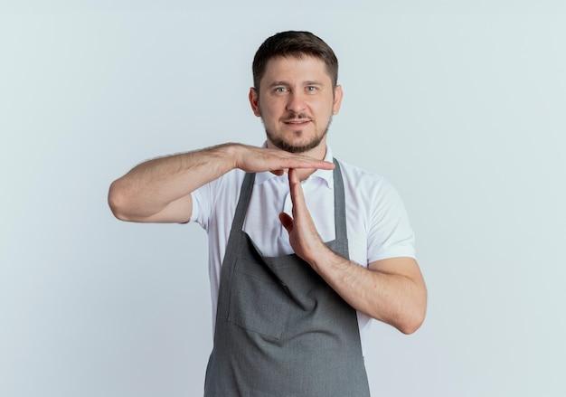 Barbeiro de avental olhando para a câmera fazendo um gesto de pausa com as mãos em pé sobre um fundo branco