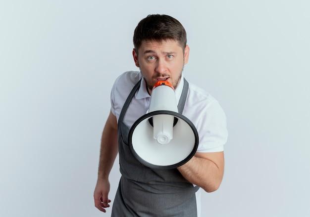 Barbeiro de avental olhando para a câmera gritando no megafone em pé sobre um fundo branco