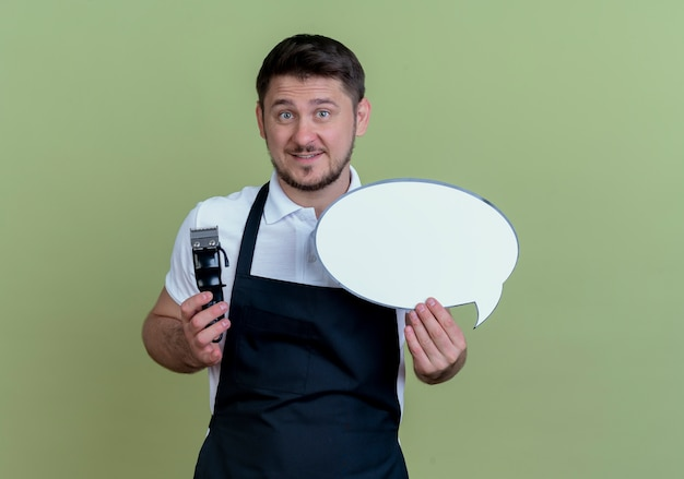 Barbeiro de avental segurando um aparador de barba e um balão de fala em branco, sorrindo com uma cara feliz em pé sobre a parede verde