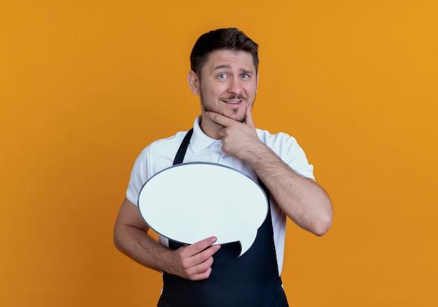 Barbeiro de avental segurando um cartaz de balão em branco com a mão em ching, sorrindo e pensando em pé sobre uma parede laranja
