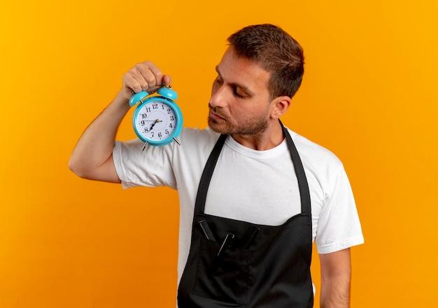 Barbeiro de avental segurando um despertador olhando para ele com uma cara séria em pé sobre a parede laranja