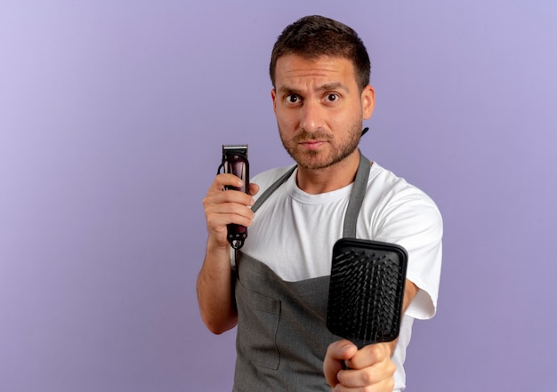 Barbeiro de avental segurando uma máquina de cortar cabelo e uma escova de cabelo olhando para a frente com uma expressão confiante em pé sobre a parede roxa
