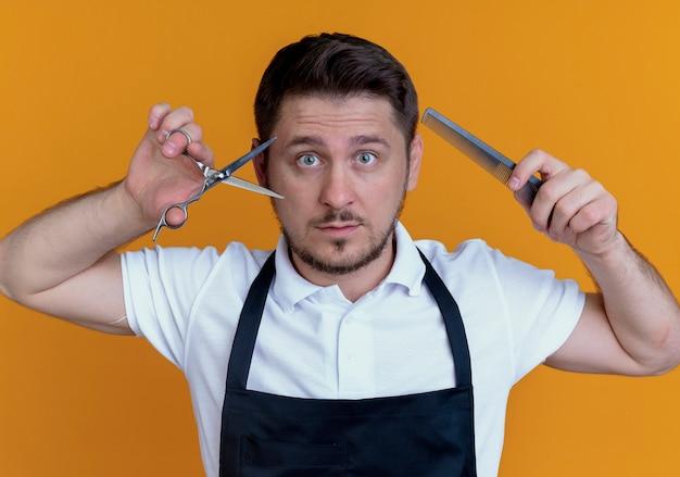 Barbeiro de avental segurando uma tesoura e um pente com olhos arregalados de pé sobre uma parede laranja