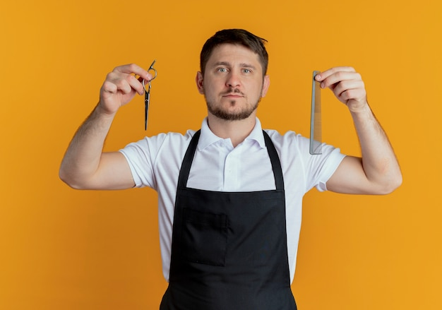Barbeiro de avental segurando uma tesoura e um pente olhando para a câmera com uma cara séria em pé sobre um fundo laranja