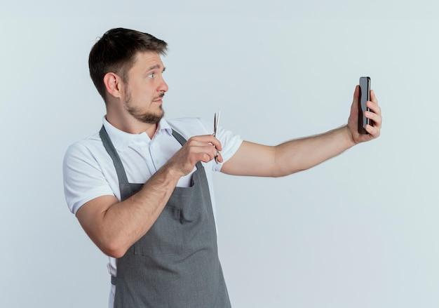 Barbeiro de avental segurando uma tesoura, tirando uma foto de si mesmo usando um smartphone em pé sobre um fundo branco