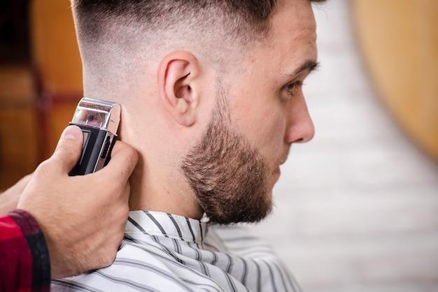 Barbeiro de close-up, terminando um corte de cabelo