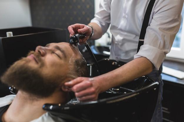 Barbeiro de colheita lavando o cabelo do homem barbudo