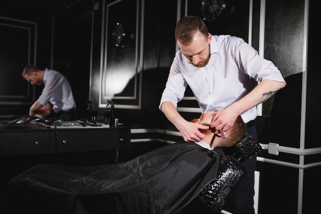 Barbeiro de visita do homem confiável na barbearia.
