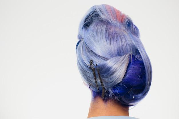Barbeiro do close up que faz o cabelo no fundo branco. cliente modelo com cabelo azul
