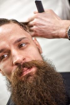 Barbeiro elegante corta um homem brutal com uma barba espessa. salão de cabeleireiro leve. homens fazem cortes de cabelo na moda.