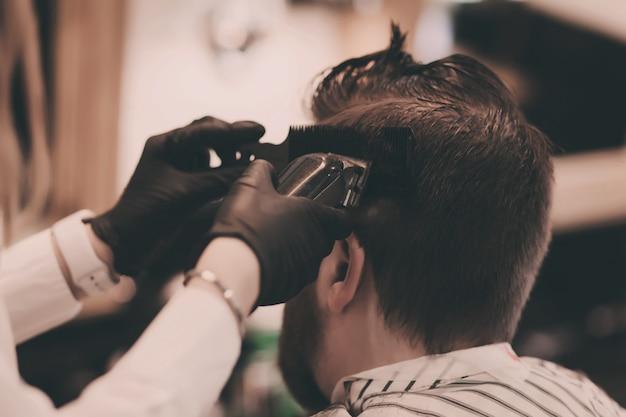 Barbeiro em luvas pretas corta o cabelo de um homem
