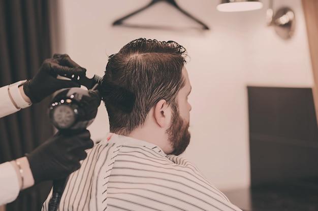 Barbeiro em luvas pretas seca a cabeça de um homem