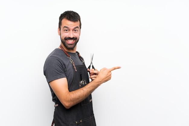 Barbeiro em um avental apontando o dedo para o lado