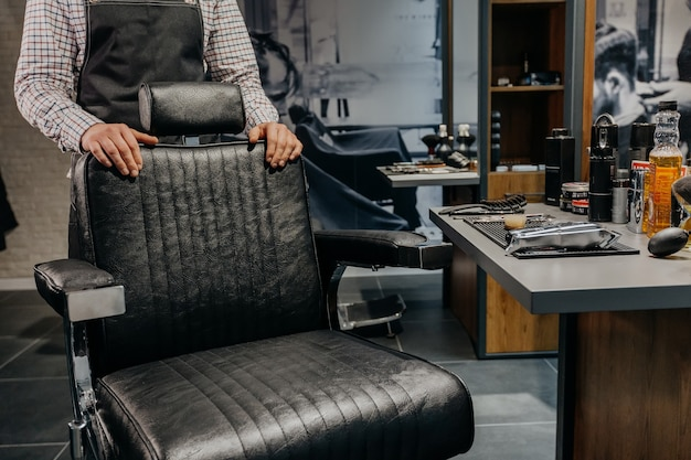 Barbeiro esperando cliente perto de uma cadeira na barbearia