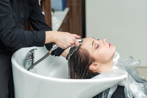 Barbeiro está lavando o cabelo da menina na barbearia