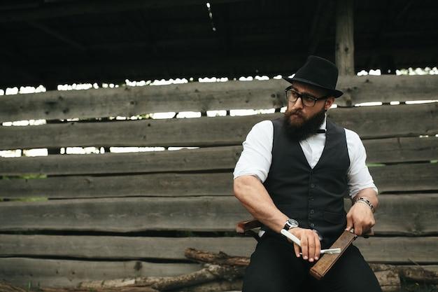 Barbeiro faz a barba de um homem barbudo ao ar livre