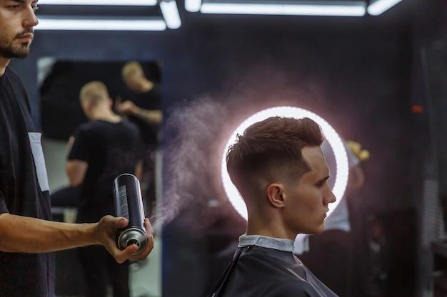 Barbeiro faz penteado com spray de cabelo após o corte de cabelo na barbearia.