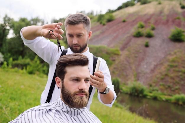 Barbeiro faz um corte de cabelo para um cliente de um homem jovem e bonita barbudo na natureza ao ar livre