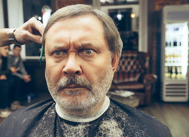 Barbeiro fazendo corte de cabelo atraente velho na barbearia