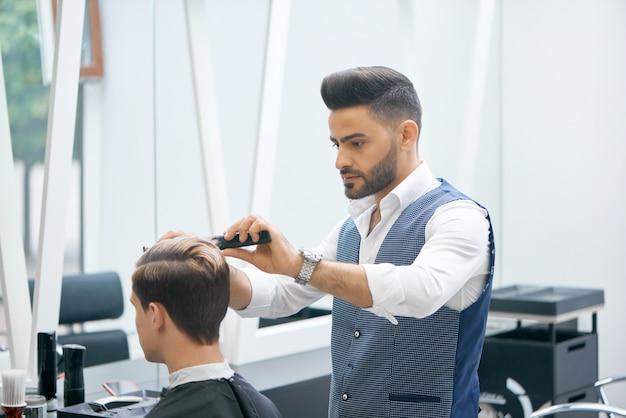 Barbeiro fazendo novo corte de cabelo para cliente jovem.