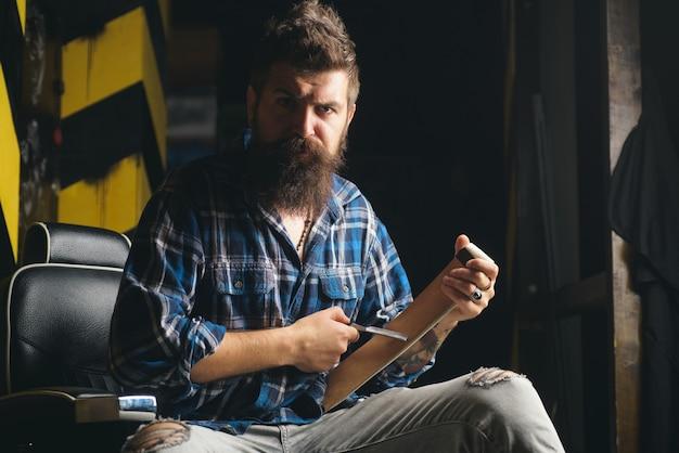 Barbeiro, fazendo o corte de cabelo de um homem barbudo atraente na barbearia. barbeiro fazendo a barba de um homem barbudo em uma barbearia.