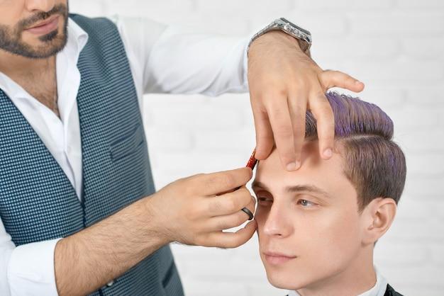Barbeiro fazendo um corte de cabelo para cliente jovem com cabelo lilás tonificado.