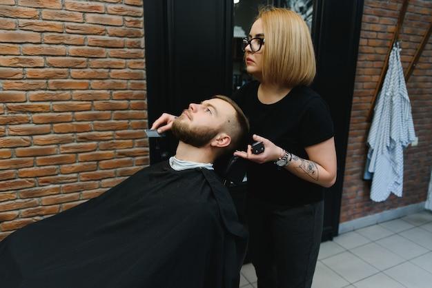 Barbeiro feminino hábil, cortando a barba de um cara moreno adulto na barbearia retrô profissional.