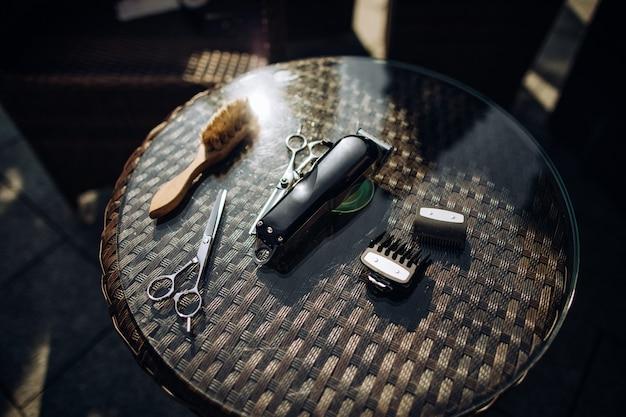 Barbeiro, ferramentas de cabeleireiro: tesoura, pente, escova, aparador na mesa