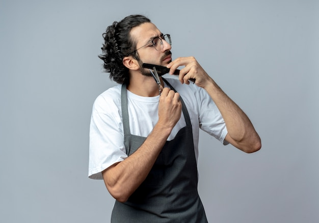 Barbeiro jovem, caucasiano, descontente, usando óculos e faixa de cabelo ondulado em uniforme, penteando e cortando a barba com os olhos fechados, isolado no fundo branco com espaço de cópia