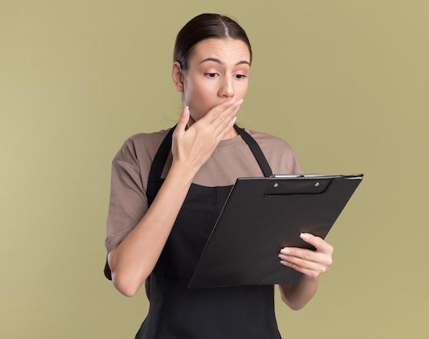 Barbeiro jovem morena chocada de uniforme coloca a mão na boca, segurando e olhando para a área de transferência isolada na parede verde oliva com espaço de cópia