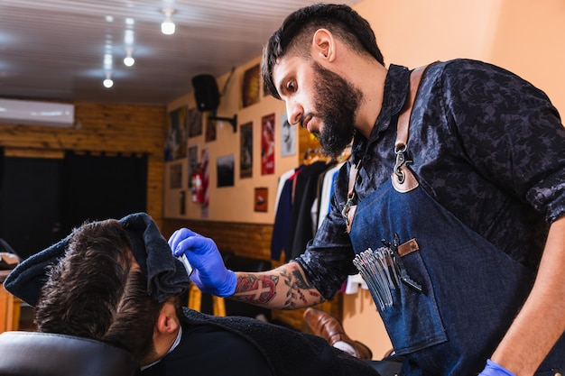 Barbeiro latino. barbearia com barbeiro trabalhando. conceito de beleza e bem-estar.