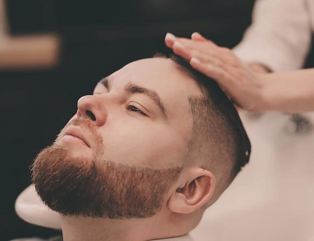 Barbeiro lavando o cabelo de um cliente barbudo em uma barbearia