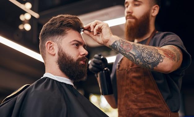 Barbeiro modelando o cabelo de um cliente