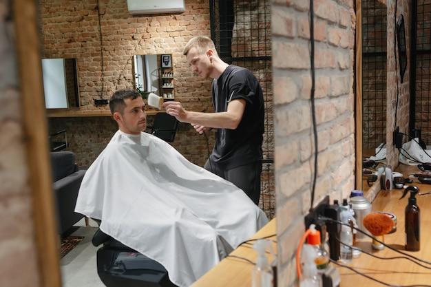 Barbeiro na barbearia atendendo cliente, fazendo corte de cabelo com máquina e pente.